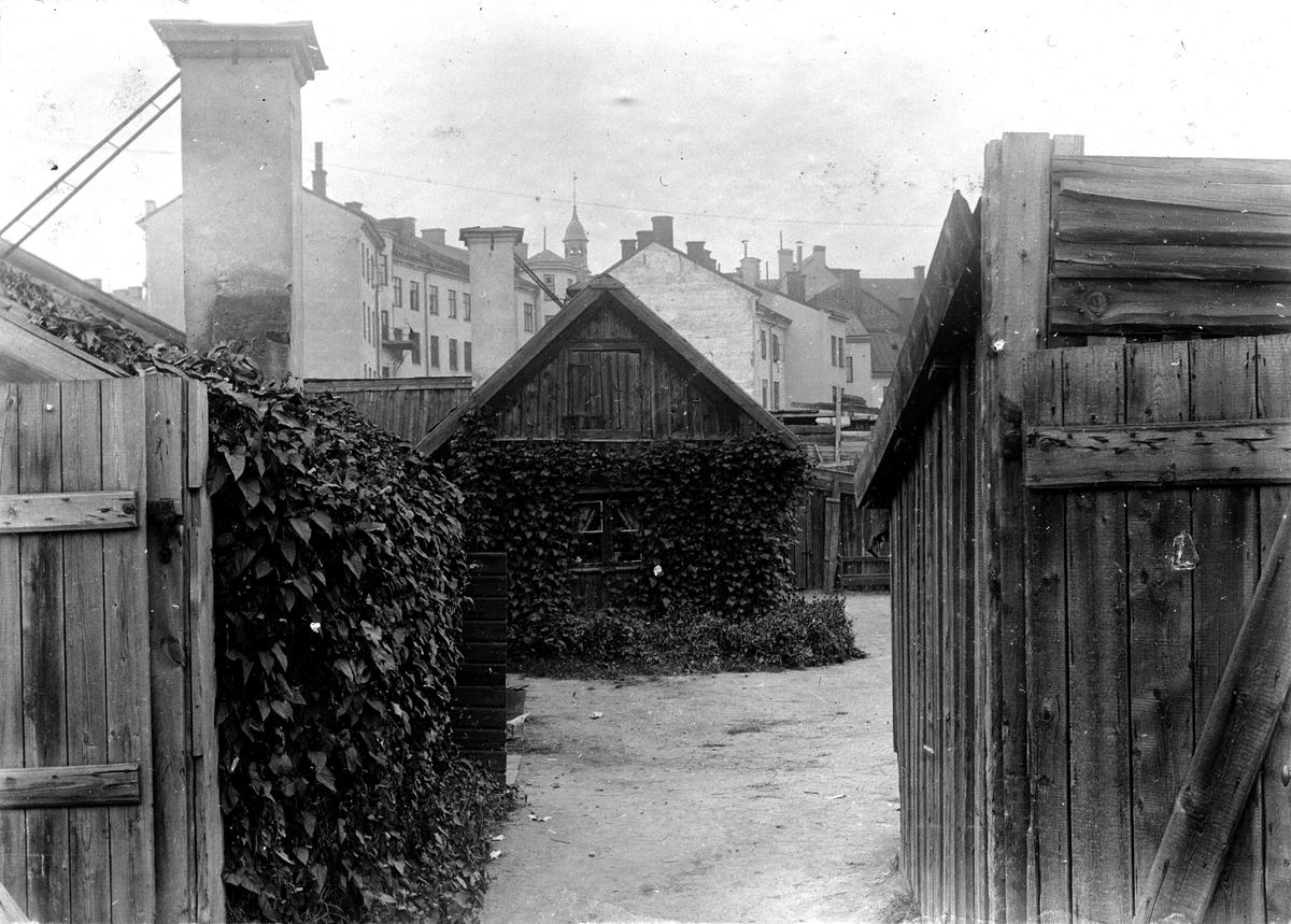 En grind som står öppen till ett bostadsområde. Fotograf Alfred Bergendahl. Givare H Bergendahl.