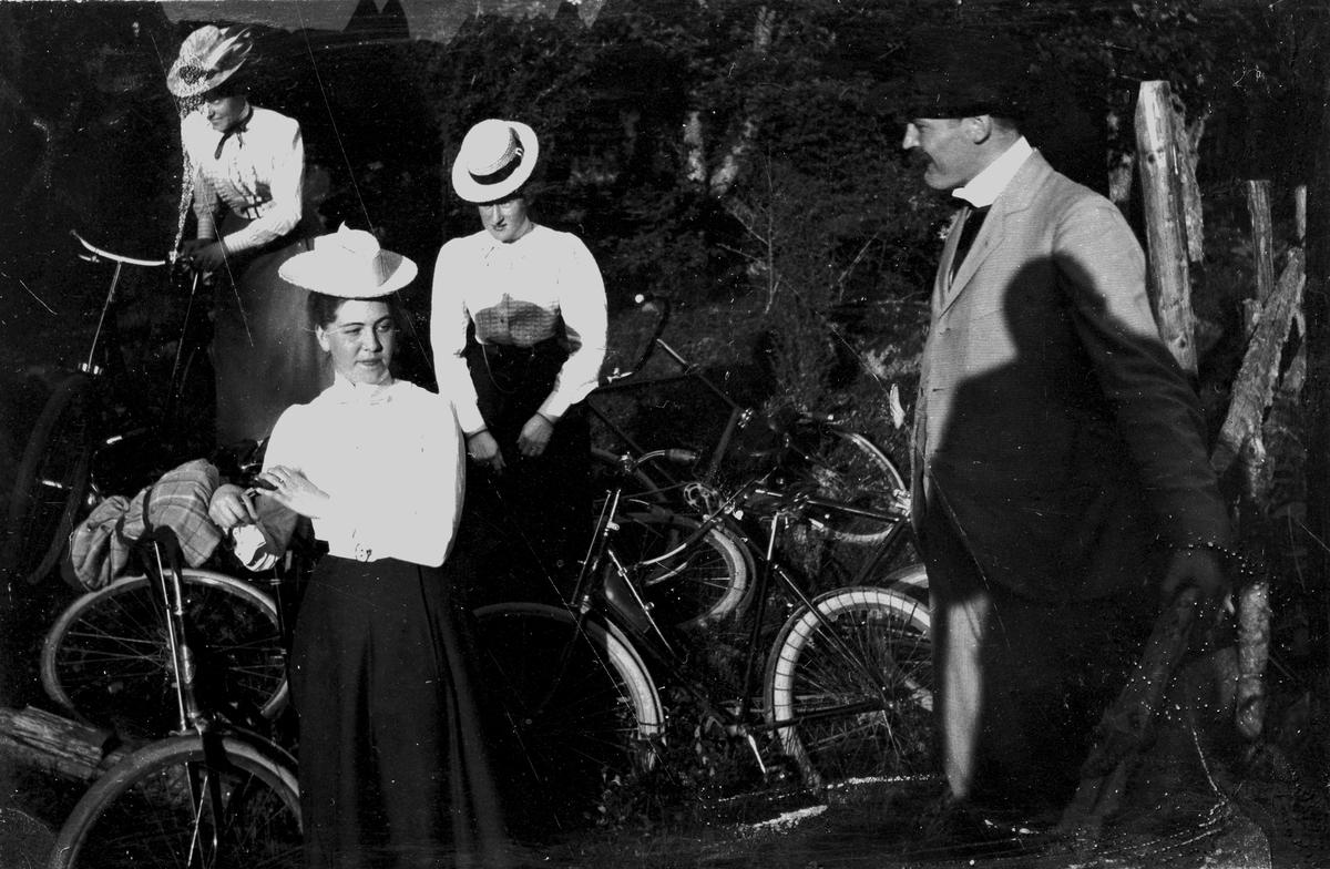 Tre kvinnor och en man med cyklar, år 1900. Fotograf Alfred Bergendahl. Givare H Bergendahl.