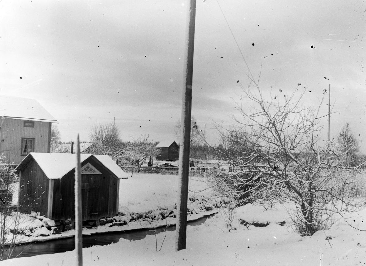 """Ågrävningen har startat men har ej kommit upp och förstört vattenspegeln för Åsmundshyttan nummer 2 """"Erkas"""". Nu är ån endast ett djup dike. """"Erkas"""" lilla gård och tvättstuga till vänster och ett gammalt magasin i bakgrunden som revs 1950."""