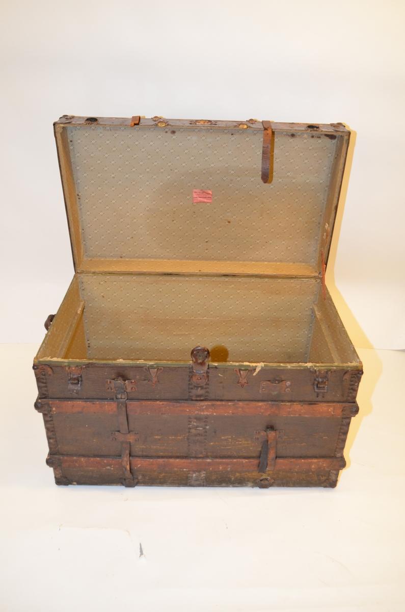Kistekasse og lokk er satt sammen av treplater, en plate for hver side av lokk og kasse, som er festet sammen med jernbeslag vertikalt langs ytterkantene og trelister på tvers av flatene, beslag og lister naglet fast til treplatene. Kasse og lokk trukket med lær. På kistens underside er treverket dekket med en tynn, svartmatl jern/aluminumsplate  som er holdt på plass av to jernbeslag langs ytterkantene på kortsidene og tre tverrgående trelister.  Håndtak i form av lærreimer på hver av kortendene, det ene avslitt.   Lokket er festet til kistekassa ved hjelp av fire jernhenglser på kistas bakside, samt et henglse på kistens innside, høyre kortside. Lokk og kasse holdes også sammen ved hjelp av to lærreimer naglet fast på kistens bakside, over lokket, og kan festes i hver sin jernspenne foran. Nøkkellås.  På innsiden er kofferten/kista trukket med mønstret stoff i grått, hvitt og grønt, limt på treverket. En tverrgående støtteliste på hver av kortsidene. Øverst i kisterommet ligger en uttakbar treskuff delt i to rom og med utskårede gripetak på hver kortside og lærhempe foran på langsiden. Skuffen trukket i samme mønstrede stoff som lokk og kisterom.
