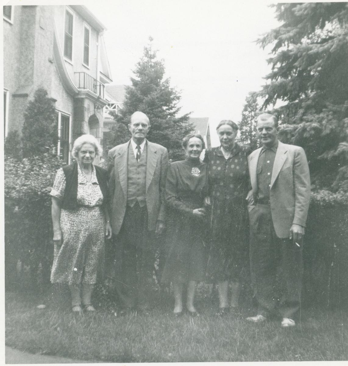 3 kvinner og 2 menn er avbildet utenfor et bolighus i Minneapolis, Amerika. Mannen lengst til høyre er Arnfinn Rosenlund (født i 1918)
