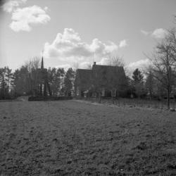 Foto av en (mindre) kyrka och en klockstapel, vid en åker.T