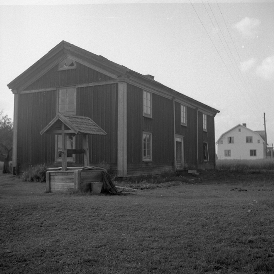 Foto av en mangårdsbyggnad. Framför syns en hink som står bredvid en brunn.