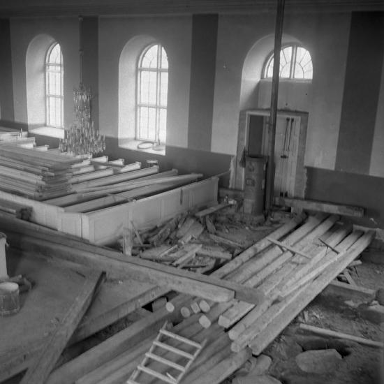 Foto av flera golvbalkar under renovering i kyrka.Torpa kyrka. Nuvarande stenkyrkan i Torpa uppfördes 1864-1865, enligt Johan Adolf Hawermans ritningar, och invigdes 17 september 1865 av biskop Henrik Gustaf Hultman. Kyrkan är uppförd i nyklassicistisk stil och består av ett rektangulärt långhus med ett halvrunt kor i öster. Tornet i väster med dubbla ljudöppningar har en lanternin med spetsgavlar och en spira krönt av ett kors.  Interiören är av salkyrkotyp. En restaurering genomfördes 1949-1951 då kyrkorummets sittplatser minskades från 800 till cirka hälften för att ge plats åt sakristia och konfirmandrum.