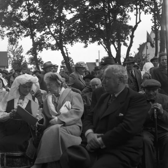 Foto av en sittande kvinna i folkdräkt (Värendsdräkt) och visar sig med något block till kvinnan som läser igenom.I bakgrunden ser man flera folk som sitter på varje bänkar, möjligen på hembygdsgård?