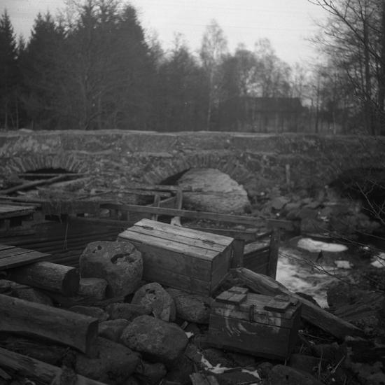 Foto av en stenvalvsbro. I förgrunden syns några fångsatanordningar för  fisk ( ). Photo  Anderbjörk c936e633a4ddb