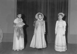 Ett grupporträtt med tre kvinnor i klänningar m.m. från börj