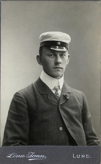 6eff8be407fa Porträtt (bröstbild, en face) av en okänd ung man i mörk, smalrandig kavaj,  studentmössa (modell Lund), vit skjorta med hög stärkkrage och randig slips,  ...
