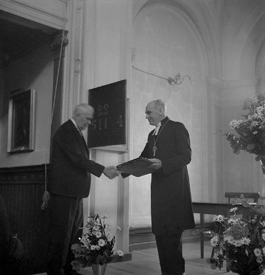 Stiftsmötet 1950. Avgående biskopen, Yngve Brilioth, mottar en gåva från enäldre man i kostym.