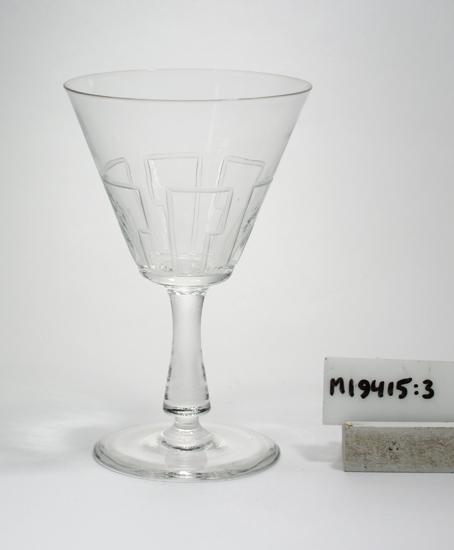 """Vitvinsglas. Formgivet av Gerda Strömberg. Möjligen tillverkat 1933.  Beskrivning: Glas på ben och fot. Omvänt konisk kupa. Runt nedre delen ingraverat ett enkelt rätvinkligt linjemönster. Färg: Ofärgat klarglas. Eventuellt halvkristall.  Mått: Ovan anges höjd och övre diameter. Glaset rymmer 12 cl. Inskrivet i huvudkatalogen 1968.  Kataloger: Hålglasform identisk med servisen """"Bero"""" 1540 - 1552, kat. 1930 och """"Bygge"""" 1580 - 1592, kat. 1930.   Gerda Strömberg (1879-1960). Glasdesigner m.m. Gift med disponent Edvard Strömberg (1872-1946) , Eda (senare flyttade man t. Strömbergshyttan, Kronob. l.) Funktion: Vitvinsglas"""