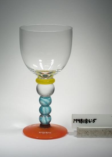 """Vitvinsglas """"Fenix"""". Art.nr. 25305. Konstnär: Kjell Engman. Beskrivning: Tulpanformad kupa, mellanring, bats, räfflat ben. Färg: Kupa av ofärgat klarglas, gul ring, turkosrandigt ben, orange fot. Mått: Ovan angivna diameter avser övre diameter. Fotdiameter: 70 mm. Stämplad märkning samt klar etikett med vit text Se """"Signering, märkning"""" ovan. Inskrivet i huvudkatalogen tidigast 1996. Funktion: Vitvinsglas"""