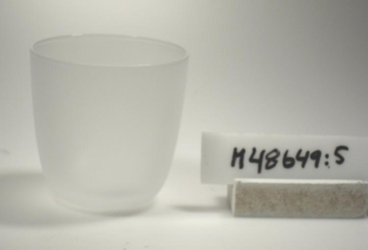 """Dricksglas/selterglas. """"UD"""" Något rundad, cylindrisk form. Hela ytan blästrad.  Gåva av bruket år 1997-05-14. Funktion: Dricksglas/selterglas"""