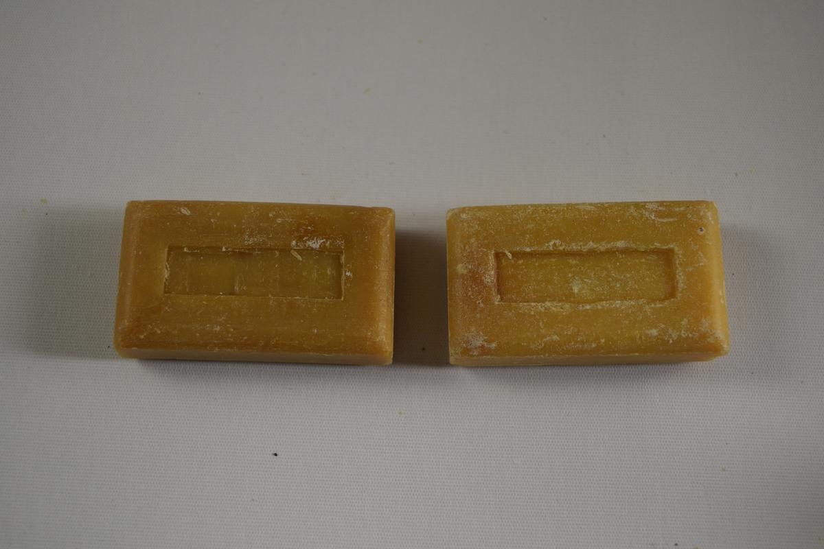 To såpestykker, rektanguær form med innskrift på ene siden og rektangulær dekor på andre siden.