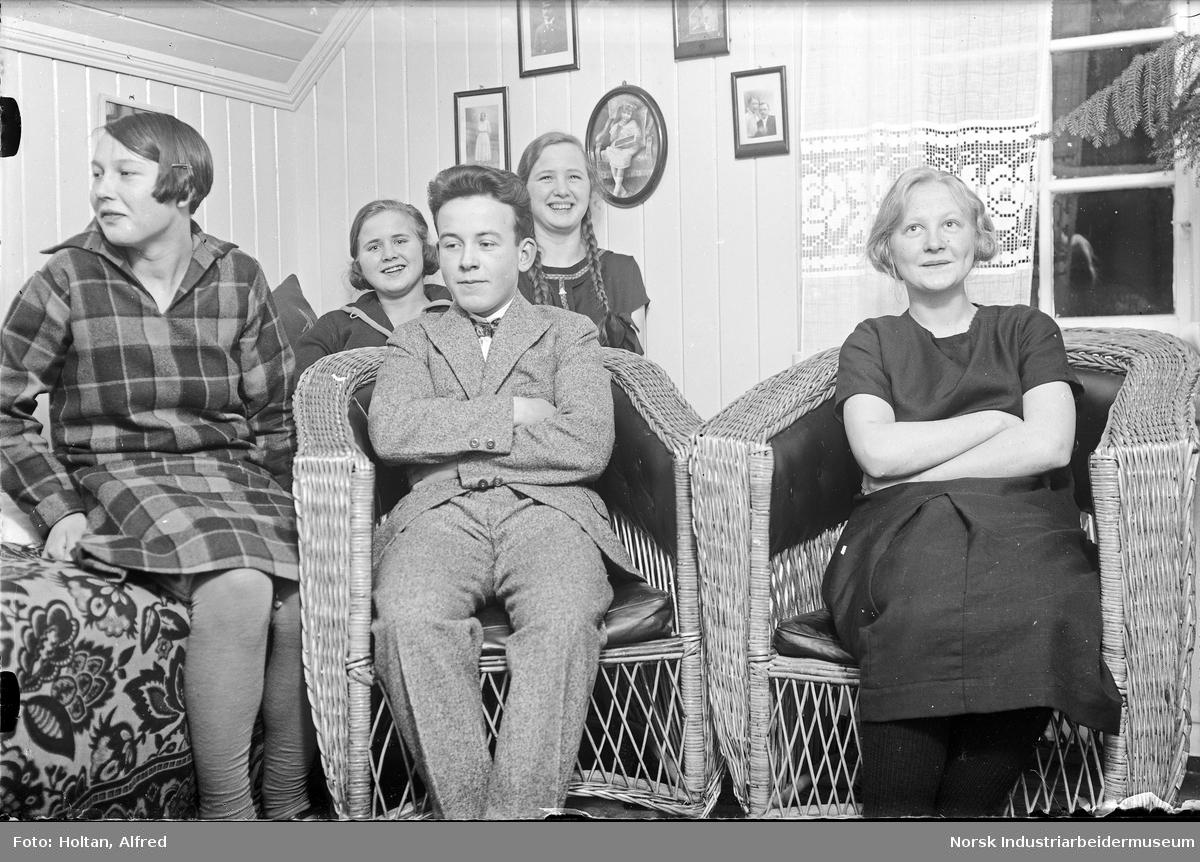 Barn i stue/soverom. Selvportrett, fotografen sitter i kurvstol i midten.