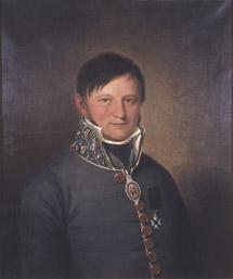 Portrett av Johan Collett. Mørk grå uniform, medalje i bånd om halsen, orden festet på brystet.