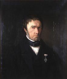 Portrett av Zacharias Mellebye. Mørk drakt, svart halsbind, hvit skjorte. Orden festet på jakkeslaget.