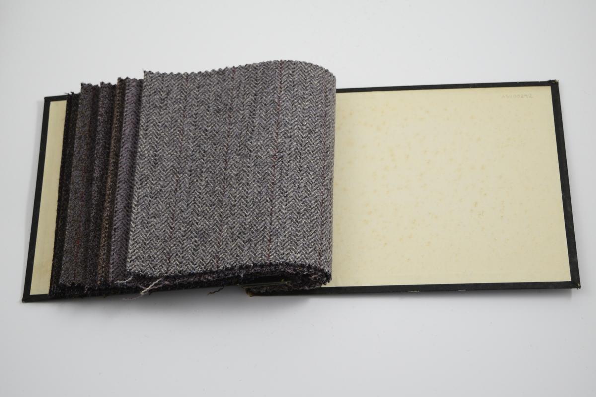 """Prøvebok med 7 prøver. Middels tykke stoff med ulike fiskebensmønster med striper. Stoffene ligger brettet dobbelt i boken. Stoffene er merket med en rund papirlapp, festet til stoffet med metallstifter, hvor nummer er påført for hånd. Påskriften på innsiden av forsideomslaget viser at alle stoffene har kvalitet """"Dovre"""".   Stoff nr.: Dovre/25, Dovre/26, Dovre/27, Dovre/28, Dovre/29, Dovre/30, Dovre/31."""