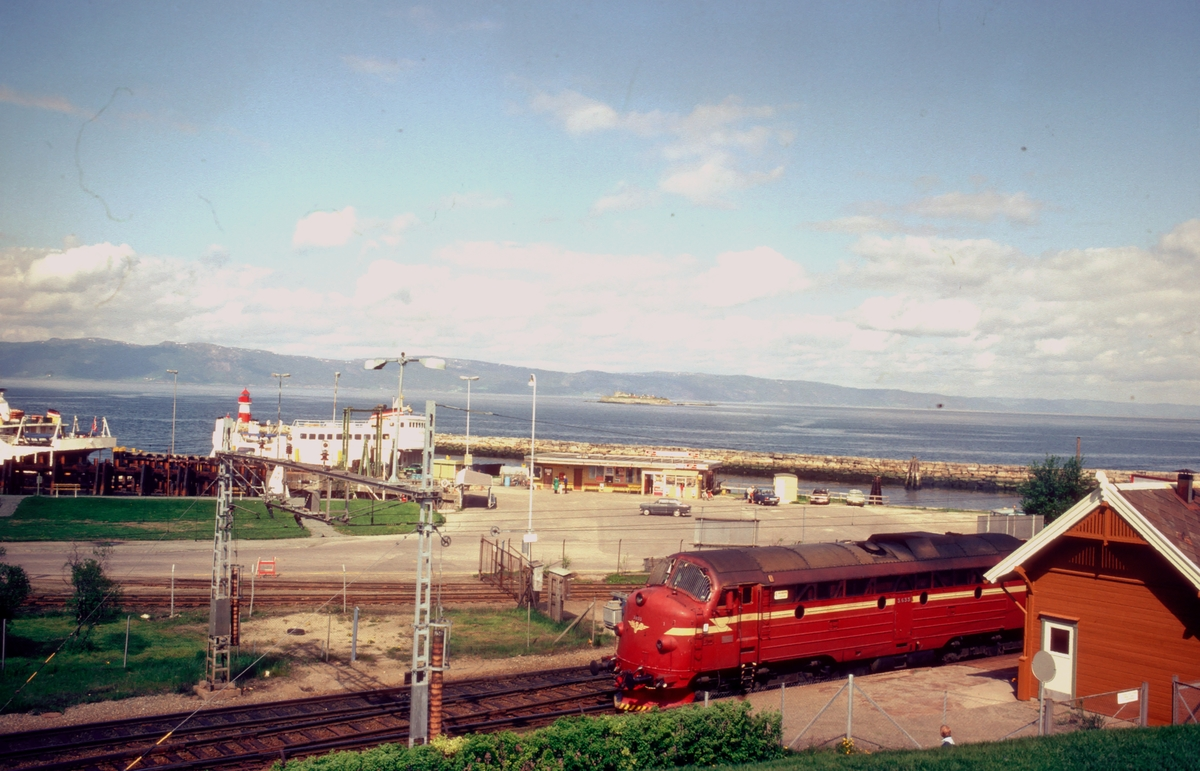 Skansen holdeplass i Trondheim. Tog til Oslo Ø over Røros med Di 3  633 passerer. I bakgrunnen fergekai til Fosen-fergen. I bakgrunnen ser vi Munkholmen.