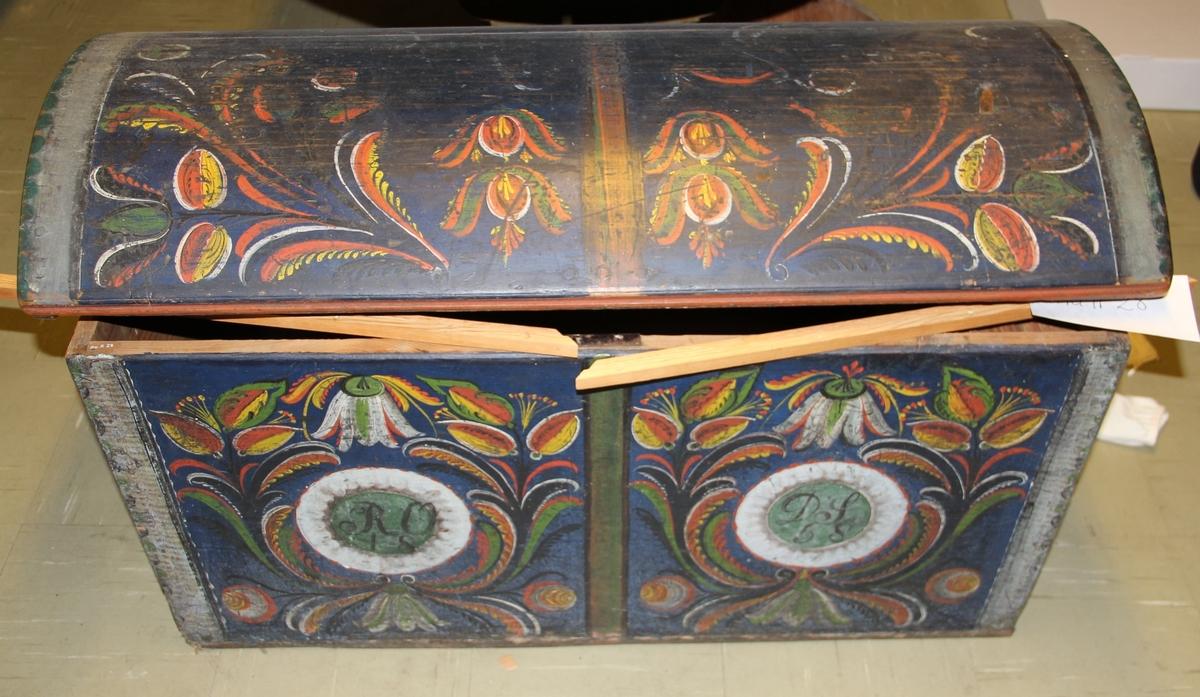 Kiste i tre med jernbeslag. Sink-konstruksjon. Rektangulær form. Hengslene smidd. Blå bunn, dekor flerfarga. Rosemaling: Ranker, tulipaner, knopper. Rosemalt av Knut A. Årstøl.