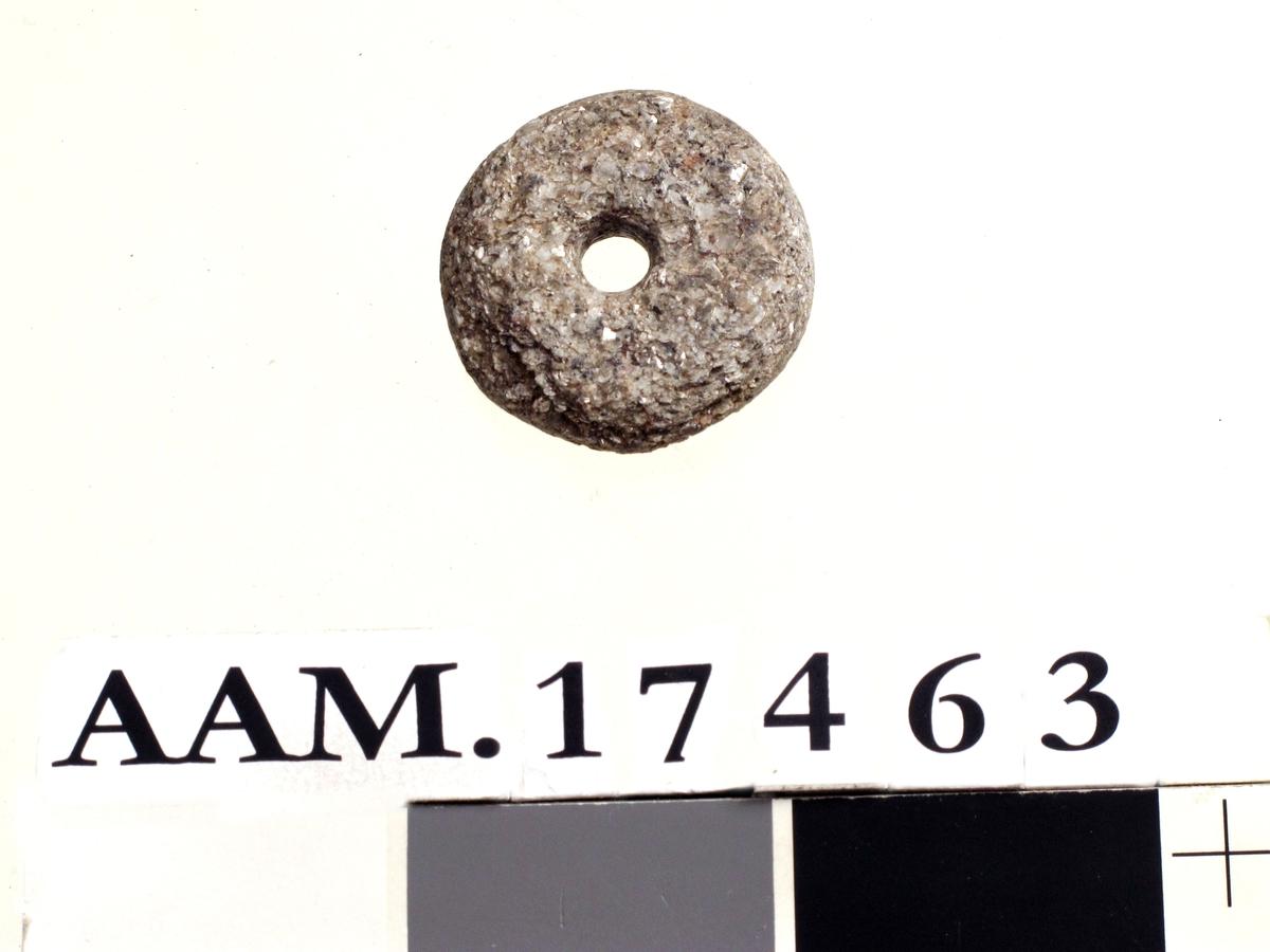 Spinnehjul, av  sterkt glimmerskimrende bergart. Form som en flat skive , litt ujevn  eller avslått i kanten.