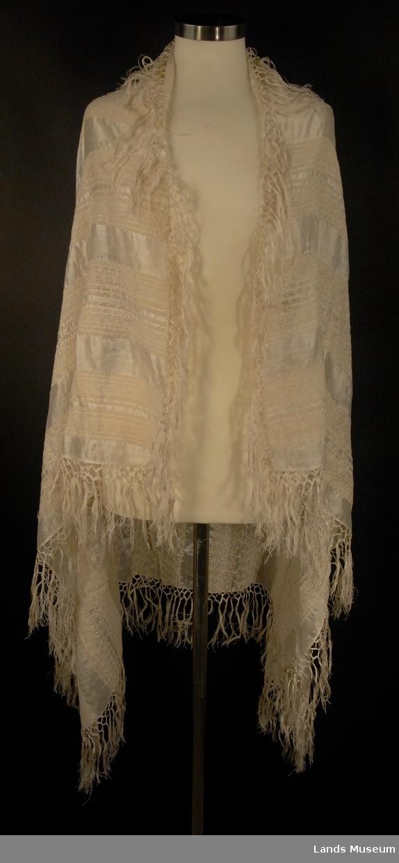 Brede striper i tykt effektgarn på en tynn toskaftsvev. Påknyttete frynser rundt heile sjalet.
