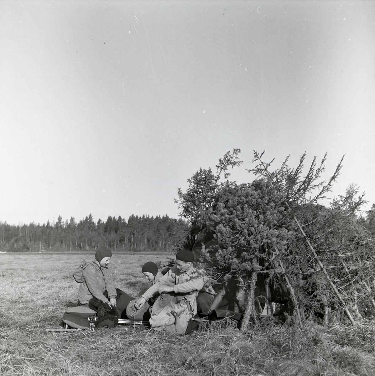 Under påsken 1954 är Hilding Mickelsson på utflykt med sina söner vid Degelmyren i Rengsjö. På ett öppet fält sitter Hilding och pojkarna vid ingången till en koja. Hilding packar ned en sovsäck i en bag och framför honom ligger kuddar och filtar. I bakgrunden syns skogen och ovanför den öppna himlen.