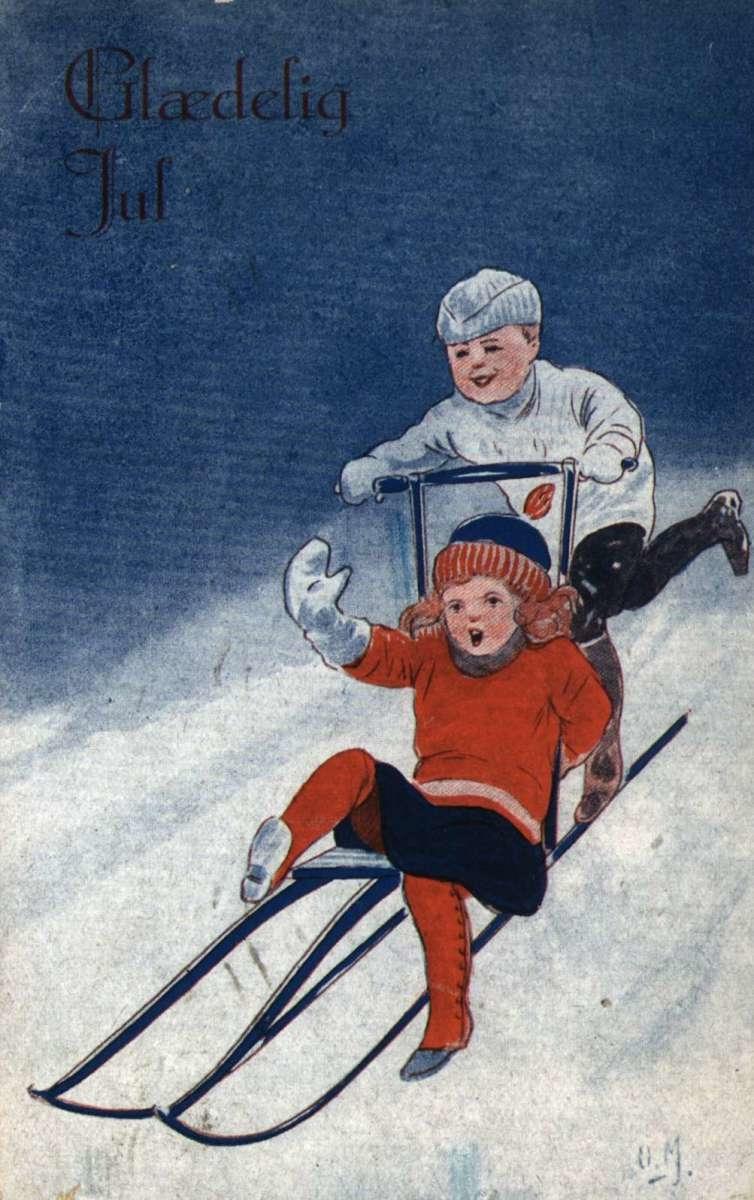Julekort. Julehilsen. Vintermotiv. Gutt og pike på spark. Illustratørs signatur O.M.  Datert 24.12.1921.