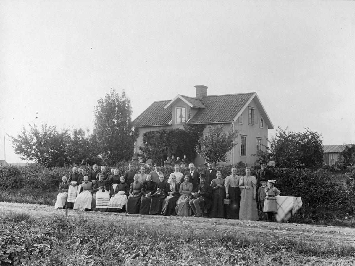Gruppfoto utanför hus, kring sekelskifte 1800-1900