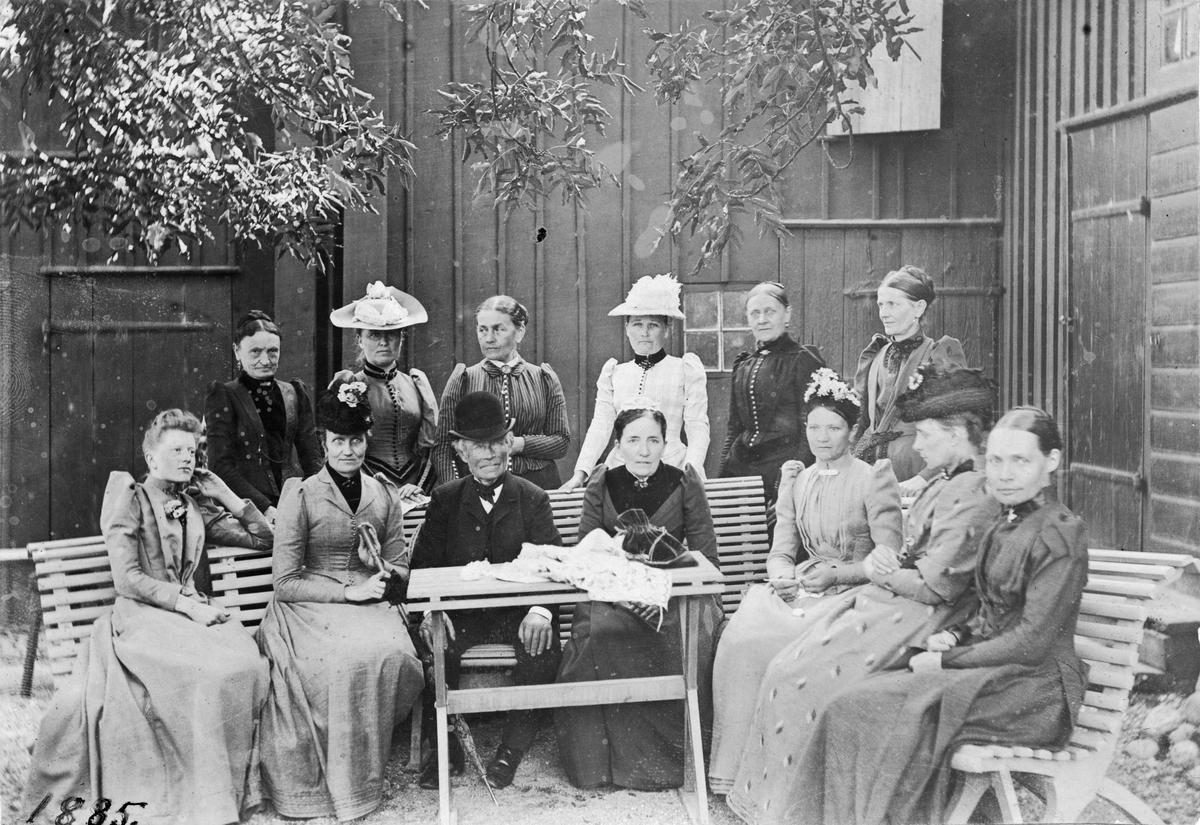Barnhemsfruarna plus äldre herre i plommonstop, på barnhemmets gård. 1885.
