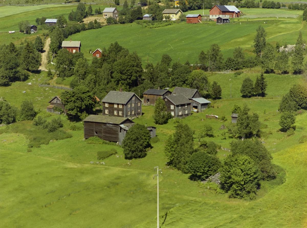Kulturlandskap. Gårdsbruk. To store tømra stuer, delvis panelt.  Gammelt uthus. Mange små hus. Dyrka mark.
