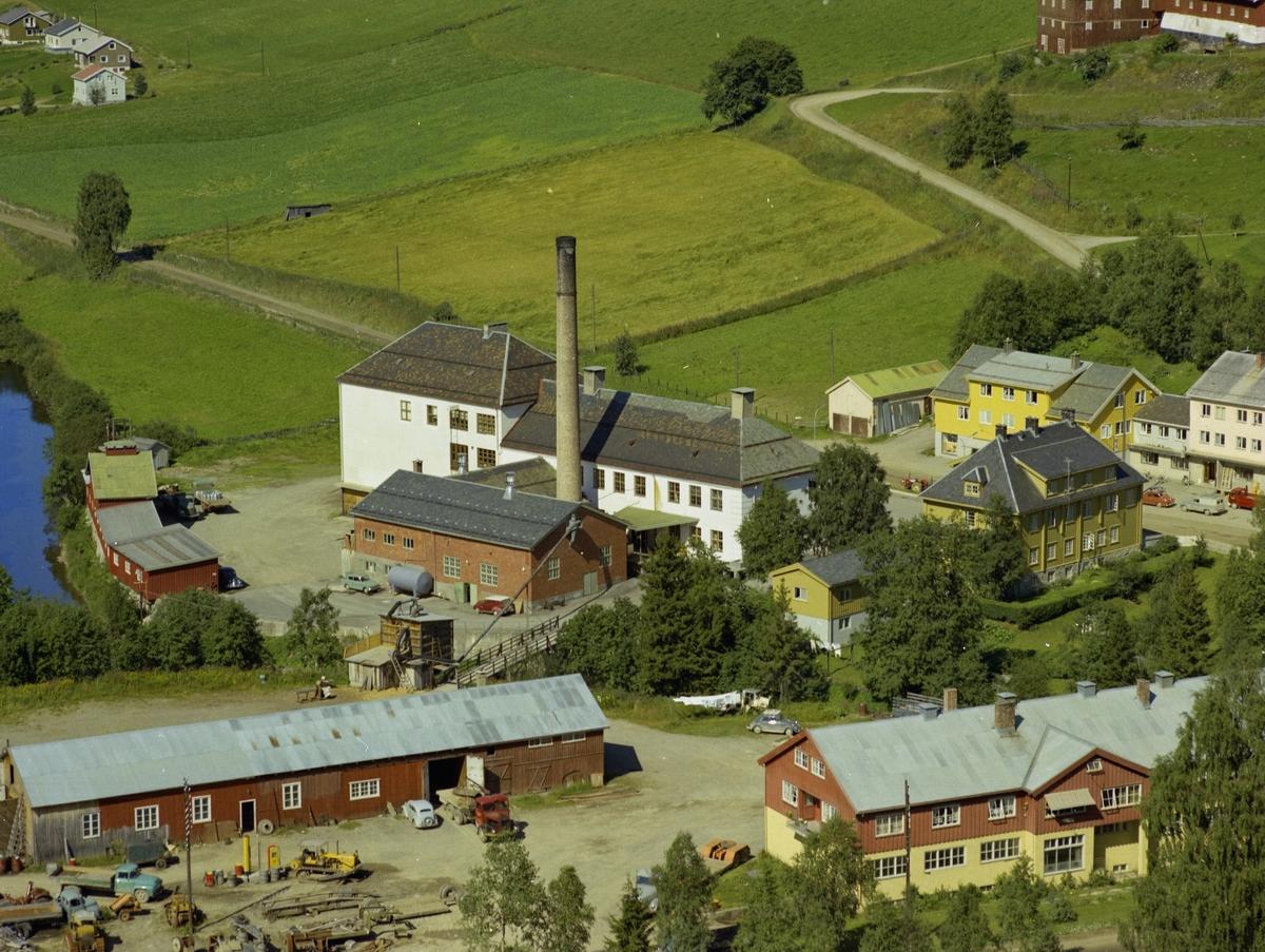 Gausdal Ysteri. Ysteribygning med høg pipe. Stor bolig- og internatbygning. Gausdal Landhandleri t.h.