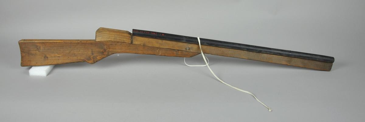 Lekevåpen i tre og plastikk. Plankedeler og PVC-rør er spikret sammen, og på siden er det festet en hvit nylonreim.