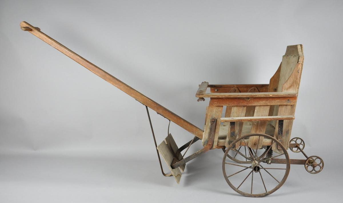 Barnetrille med en størrelse som tilsier at den ble laget for barn rundt 3-5 år. Stolen er trekt med stoff. Nærmest alle metalldeler på vognen er tilrustet. En tredel fremst på stolen (til høyre) er knekt av.