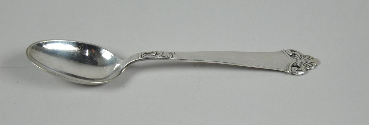 Skje med navnet Silhouet - akantusmotiv med skjell på enden av skaftet, mindre akantusmotiv mot bladet..
