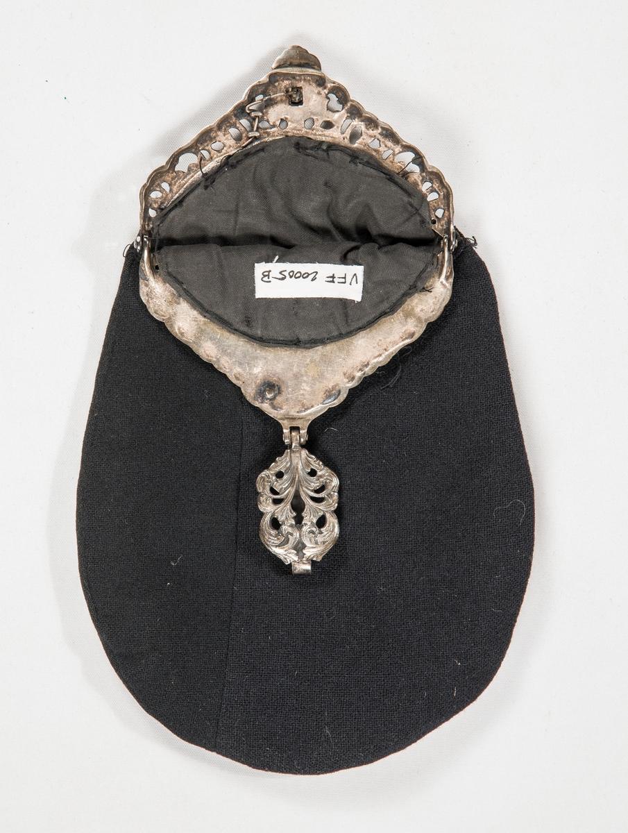 Valdresbunad i svart ulltøy med kulørt ullbroderi. Stakk, A og lomme, B. Stakken er fora i rygg og framstykke med eit lysare ullstoff.