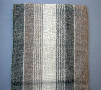 Vävprov i tuskaftsbindning med ullgarn i varp och inslag. Breda ränder i natursvart (2 st), brunt (2 st) och naturvitt (1 st) med smala ränder i samma färger.