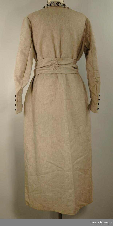 Kjole med langskinkearm, krave, brystduk og belte. Lissebroderi på erme, krage og hals. Sorte knapper.