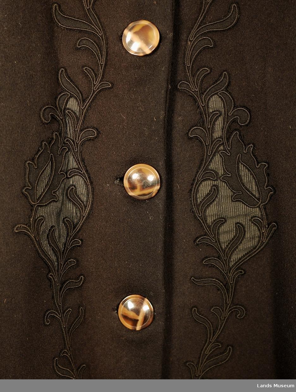 Sort lissebroderi på kraven og rundt nedentil, 6 knappehull. Stor krave, brunlege knapper og belte. Tykt frakkeklede i bol. Kypertvevd ulltøy i ermer, svakt stripete. Ermene ser ut til å vere gjenbruk. Tøyet minner om dresstøy. Maskinprodusert bord med negativ og positiv applikasjon og lissebroderi i koftehøgde og på kragen. Kragen har tre store tunger og er kantet med et tunget flettebånd. Ermene er fôret med blomstrete bomullstøy.
