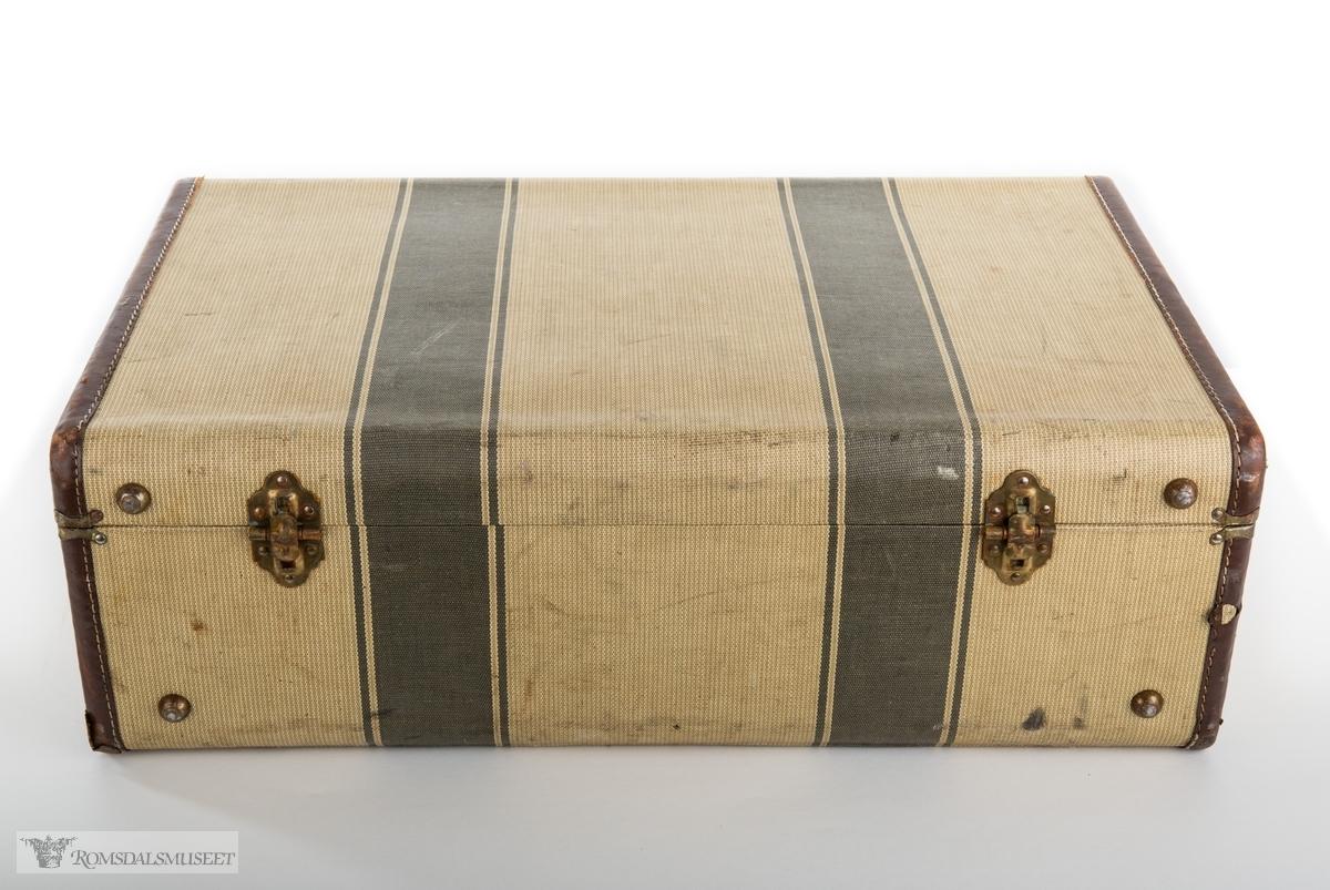 Rektangulær koffert i herdet lerret med forsterkninger av skinn, skinnhåndtak og beslag og lås i messing. Kofferten er kleed med lilla nylonstoff og fire rysjede lommer er sydd inn i trekket på innsiden av lokket og på koffertens sider.