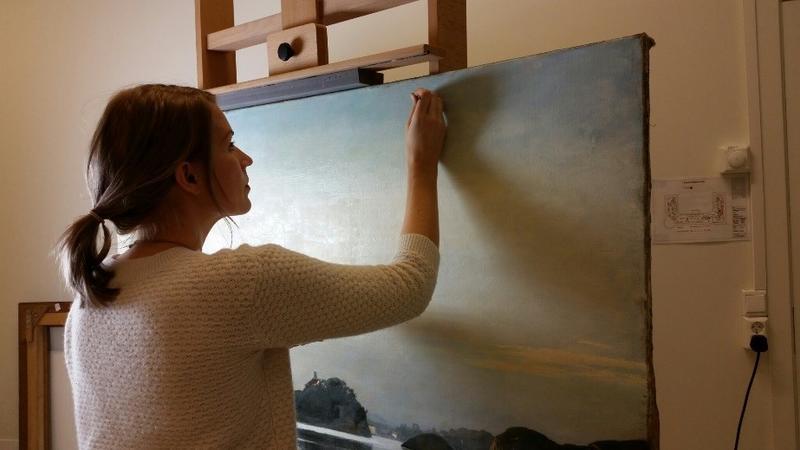 Gjenstands- og malerikonservator Kristine Draugedalen renser et landskapsmaleri. Foto: MiA. (Foto/Photo)