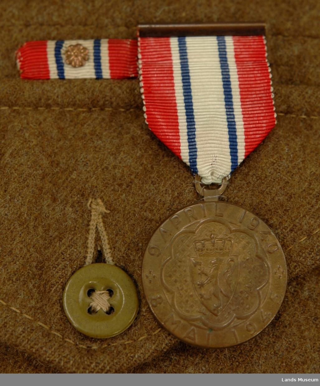Uniform som består av: Jakke med armbind, bukse, lue/barett, belte og gamasjer/anklets.  Uniformen er i vadmel og militærgrønnfarge. Armbindet er i strie med det norske flagget påsydd. Armbindet er påsydd venstre arm.  Jakka er kort, str. 9. På innsiden er det trykket stoffmerke. Over ytterlommen sitter det ei medalje og eit rektangulært flagg med ein metallrose på midten.  Buksa har 2 lommer foran og 1 bak.  Lua/baretten har bomullsfôr inni. I front på lua sitter Haakon 7'merke med lauvbærkrans rundt.