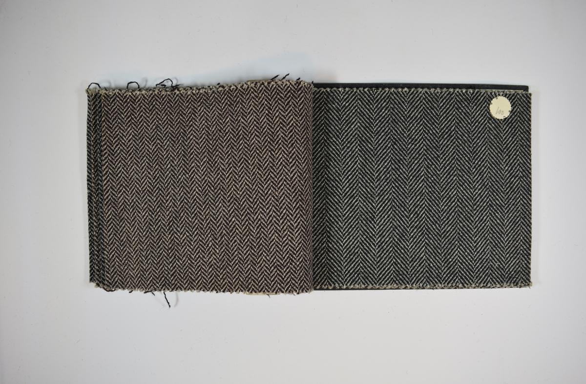 Prøvehefte med 6 prøver. Middels tykke stoff med fiskebensmønster. Stoffene ligger brettet dobbelt i heftet. Stoffene er merket med en rund papirlapp, festet til stoffet med metallstifter, hvor nummer er påført for hånd. Heftet har stiv bakplate og en papp-plate der heftet er stiftet som dekker ca. 5 cm forsiden. På pappen på forsiden er det en innskrift som indikerer at alle stoffene har kvaliteten 175B.   Stoff nr.: 175B/27, 175B/28, 175B/35, 175B/36, 175B/100, 175B/101.