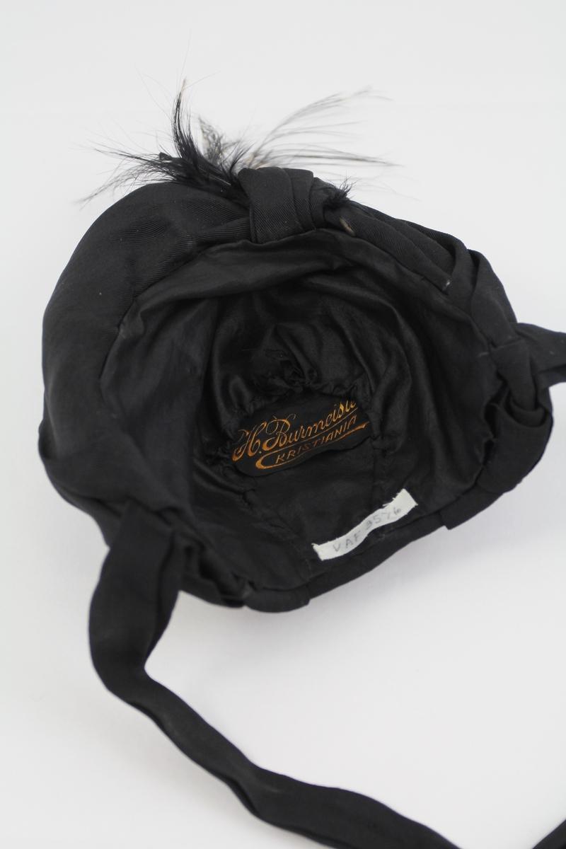 Ørehatt,sort silkerips over virrestativ. Hatten er rett avkuttet bak i nakken, stoffet er drapert over bakhodet og er fran arrangert til en opprettstående karm som går fra øre til øre. Karmen er pyntet med et tverrbånd og frem fra dette reiser seg en dusk av sorte strålefjær med enkelte hvite spetter. Knytebånd ved ørene. Nakkelinjens innvendige mål ca. 24 cm
