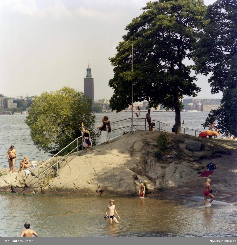 Badande människor vid Långholmsbadet, Stockholm. I bakgrunden Stockholms stadshus.