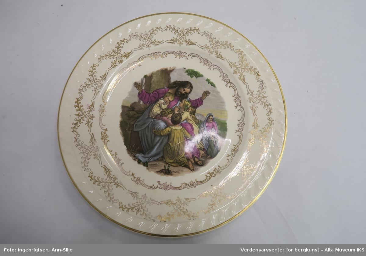 Runde fat med opphengshempe på baksiden. Gjenstand A har bilde av Jesus og barna, og gjenstand B  er det avbildet to jenter i hardangerbunad.