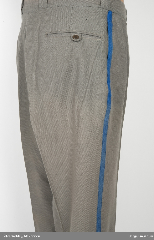 Buksene er grå med en kornblå stripe nedover fra linningen fra begge sider. Buksene har sidelommer, baklomme og en liten lomme foran. Linningen er foret. Det er brodert TH i linningen bak, antagelig initialene til brukeren av buksa.
