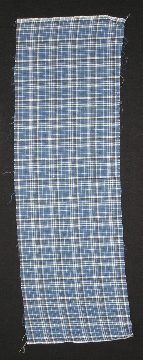 Bomullstyg till klänning, 22 x 68 cm, tuskaft, blå botten, svarta och vita ränder bildande oregelbundna rutor  Katalogiserad av Karin Nordenfelt, Elisabet Stavenow, Marie-Louise Wulfcrona-Dagel.