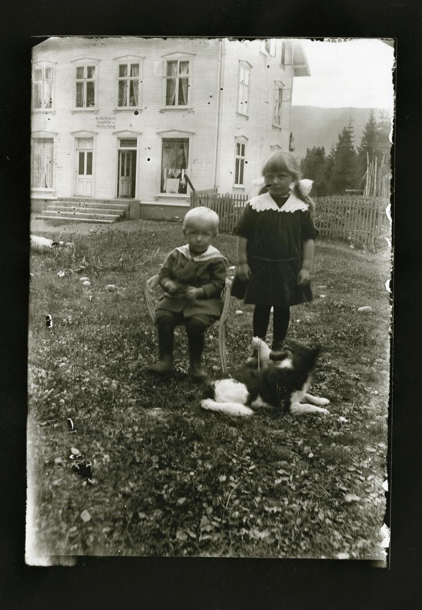 To barn står foran ett hvitt hus som var en motebutikk.
