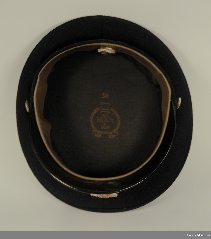 Blank skygge, emblem i front, dobbelt snor. 1 knapp på hver side.
