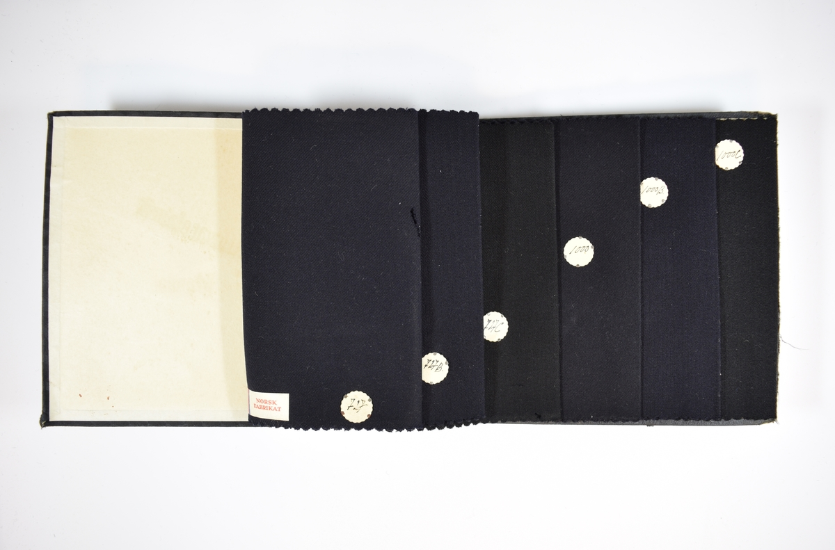 Prøvebok med 6 stoffprøver. Relativt tynne ensfargede mørkeblå eller sorte stoff med fiskebensmønster eller skrå striper som vevmønster. Kyperbinding/diagonalvevd. Stoffene ligger brettet dobbelt slik at vranga skjules. Stoffene er merket med en rund papirlapp, festet til stoffet med metallstifter, hvor nummer er påført for hånd. Alle stoffene har også en klistrelapp nesten midt på, nederst.   Stoff nr.: 727, 727B, 727C, 1000, 1000B, 1000C.